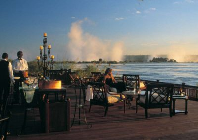 Royal Livingstone Hotel Sundeck on the banks of the Zambezi River with the plume of Victoria Falls in the background
