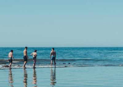 Beach goers taking a dip, Buffles Bay Beach, South Africa